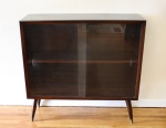 Mid century modern mini bookcase with splayed legs and glass doors